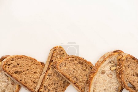 Photo for Top view of whole grain bread slices on white background with copy space - Royalty Free Image