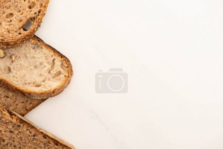 Photo for Top view of tasty whole grain bread slices on white background with copy space - Royalty Free Image