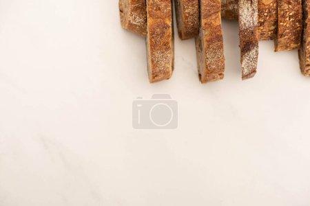 Draufsicht auf leckere Vollkornbrotscheiben auf weißem Hintergrund mit Kopierfläche