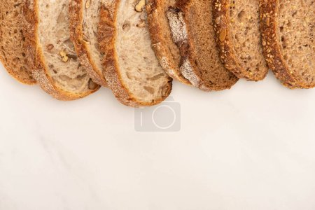 Photo for Top view of fresh whole wheat bread slices on white background - Royalty Free Image