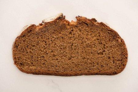 Draufsicht auf frische braune Brotscheibe auf weißem Hintergrund