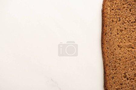 Draufsicht auf frische braune Brotscheibe auf weißem Hintergrund mit Kopierfläche