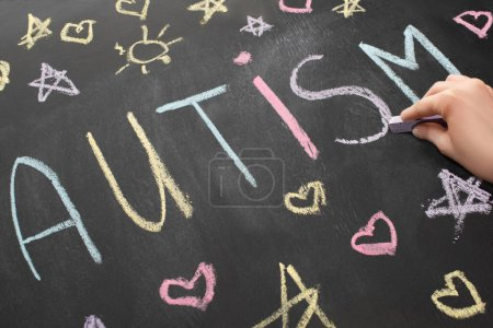 Photo for Partial view of woman writing word autism on chalkboard - Royalty Free Image