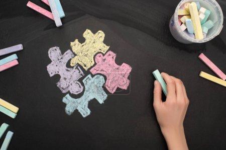 Photo pour Vue du dessus de la femme tenant de la craie turquoise à bord avec dessin puzzle pour la Journée mondiale de sensibilisation à l'autisme - image libre de droit