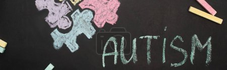 Photo for Panoramic shot of chalkboard with word autism and puzzle drawing - Royalty Free Image