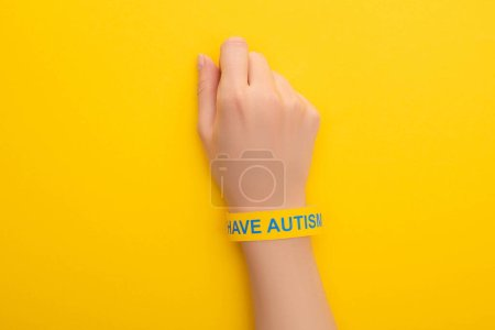 Photo for Top view of woman hand in bracelet with I have autism inscription on yellow - Royalty Free Image