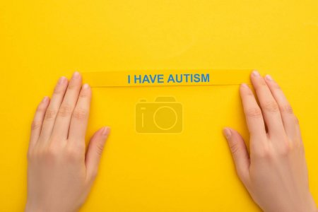 Photo pour Vue partielle d'une femme tenant un bracelet avec j'ai l'autisme inscription sur jaune - image libre de droit