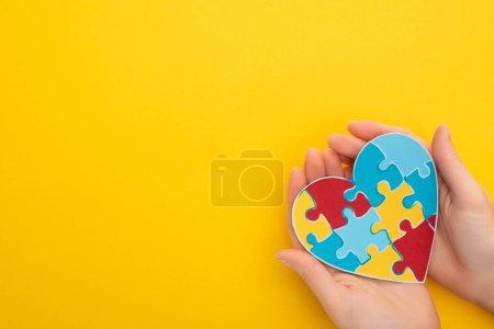 Photo pour Vue partielle de la femme tenant le coeur coloré de puzzle sur le jaune pour la Journée mondiale de sensibilisation à l'autisme - image libre de droit