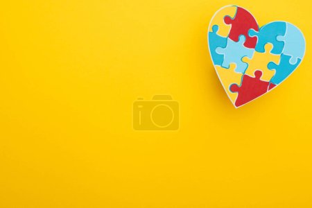 Photo for Top view of colorful heart with puzzle on yellow for World Autism Awareness Day - Royalty Free Image