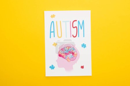 Photo for Top view of paper sheet with autism lettering and drawing of child isolated on yellow - Royalty Free Image