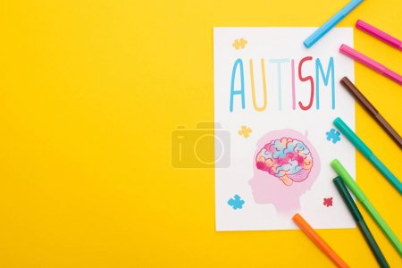 Photo for Top view of felt pens on paper sheet with autism lettering and drawing of child isolated on yellow - Royalty Free Image