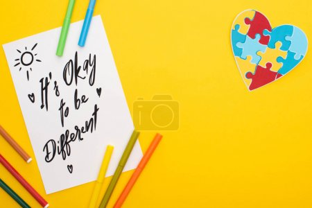 Photo for Top view of felt pens on paper sheet with its okay to be different inscription and puzzle heart isolated on yellow - Royalty Free Image