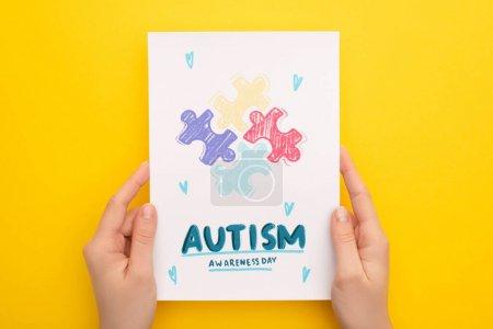 Photo pour Crochet vue d'une femme tenant une carte avec casse-tête pour la Journée de sensibilisation à l'autisme en jaune - image libre de droit