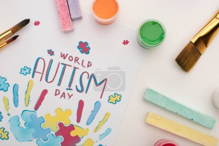 Photo for Top view of card with World Autism Day lettering and painting of puzzle and hand prints on white with paint brushes, chalks and paints - Royalty Free Image