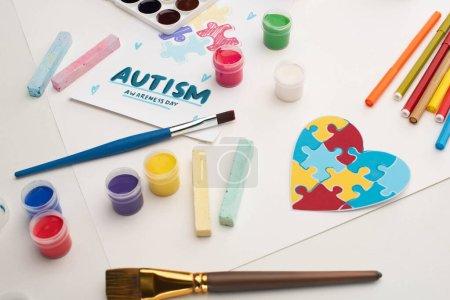 Photo pour Carte avec Journée de sensibilisation à l'autisme lettrage et peinture de puzzle sur blanc avec pinceaux, craies, marqueurs et coeur de puzzle - image libre de droit