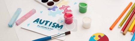Photo pour Prise de vue panoramique de la carte avec lettrage Journée de sensibilisation à l'autisme et peinture de puzzle sur blanc avec pinceaux, craies et marqueurs - image libre de droit