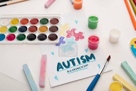 Photo pour Carte avec Journée de sensibilisation à l'autisme lettrage et peinture de puzzle sur blanc avec peintures et craies - image libre de droit