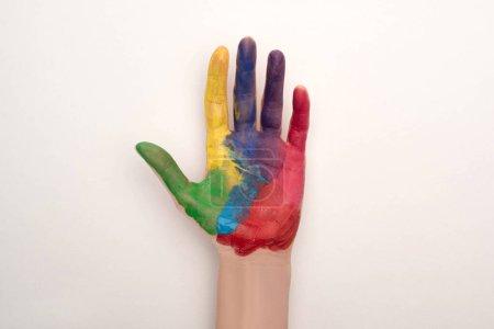 Photo pour Vue recadrée de la main féminine avec peinture colorée sur blanc pour la Journée mondiale de sensibilisation à l'autisme - image libre de droit