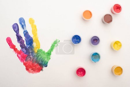 Photo for Top view of colorful handprint and paints on white for World Autism Awareness Day - Royalty Free Image