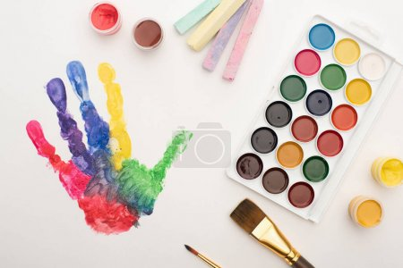 Photo for Top view of colorful handprint, chalks, paint brushes and paints on white for World Autism Awareness Day - Royalty Free Image