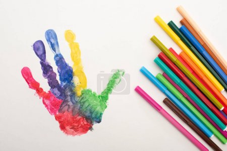 Photo pour Vue du dessus de l'empreinte de main colorée et stylos plats sur blanc pour la Journée mondiale de sensibilisation à l'autisme - image libre de droit