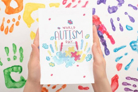 Photo for Cropped view of woman holding card with World Autism Day lettering and puzzle on white with hand prints - Royalty Free Image