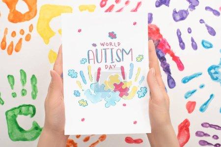 Photo pour Vue recadrée de la femme tenant la carte avec le lettrage Journée mondiale de l'autisme et puzzle sur blanc avec des empreintes de main - image libre de droit