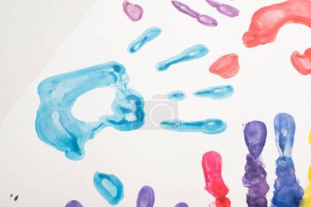 Photo pour Vue du haut des empreintes de mains colorées sur blanc pour la Journée mondiale de sensibilisation à l'autisme - image libre de droit
