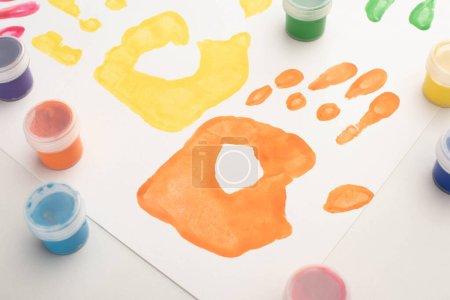 Photo pour Le gros plan des empreintes et des peintures colorées sur blanc pour la Journée mondiale de la sensibilisation à l'autisme - image libre de droit