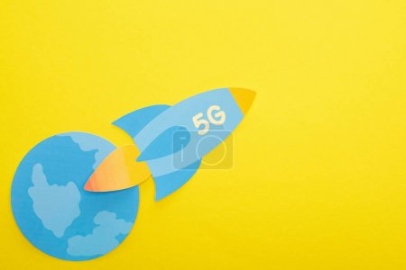 Photo for Top view of paper rocket with 5g lettering near globe on yellow background - Royalty Free Image