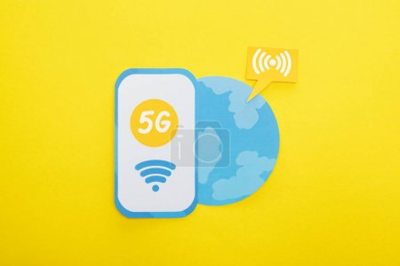 Photo for Top view of 5g lettering on paper smartphone near globe on yellow background - Royalty Free Image