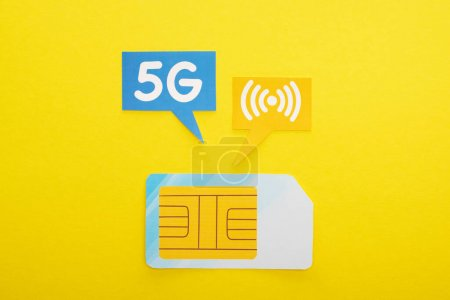 Photo pour Vue du dessus de la carte SIM et bulles de parole avec lettrage 5g sur fond jaune - image libre de droit