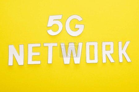 Photo pour Vue du dessus du lettrage réseau blanc 5g sur fond jaune - image libre de droit