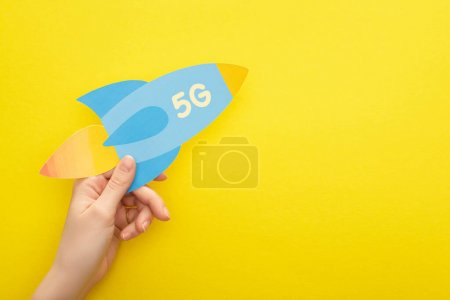 Photo for Cropped view of woman holding paper rocket with 5g lettering on yellow background - Royalty Free Image