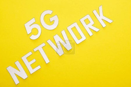 Photo for Top view of white 5g network lettering on yellow background - Royalty Free Image