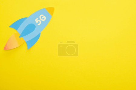 top view of paper rocket with 5g lettering on yellow background