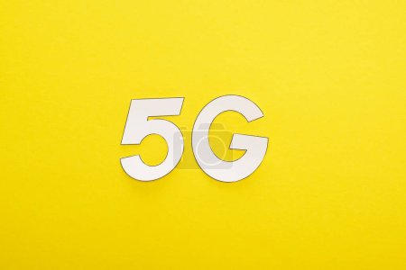 Photo for Top view of white 5g lettering on yellow background - Royalty Free Image