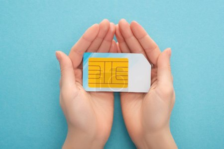cropped view of woman holding sim card on blue background