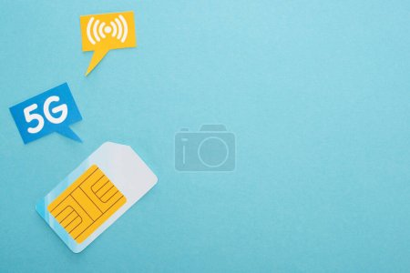 top view of sim card and  speech bubbles with 5g lettering on blue background