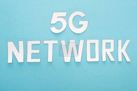 Photo pour Vue du dessus du lettrage réseau blanc 5g sur fond bleu - image libre de droit