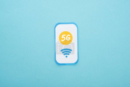 top view of 5g lettering on paper smartphone on blue background