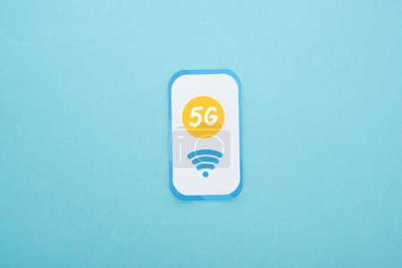 Photo for Top view of 5g lettering on paper smartphone on blue background - Royalty Free Image