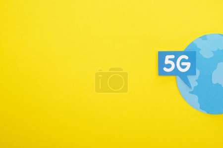 Photo for Top view of speech bubble with 5g lettering near blue globe on yellow background - Royalty Free Image