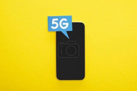 Photo pour Vue du haut de la bulle vocale avec lettrage 5g près du smartphone sur fond jaune - image libre de droit