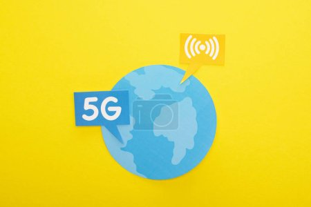 Photo for Top view of globe and 5g lettering on yellow background - Royalty Free Image