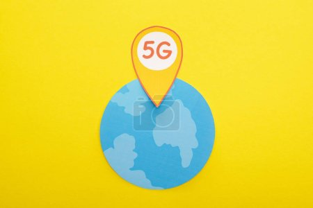 top view of globe and 5g lettering in location mark on yellow background