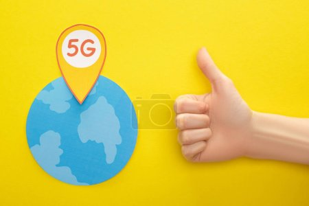 top view of globe and 5g lettering in location mark near thumb up on yellow background