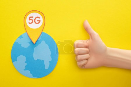 Photo for Top view of globe and 5g lettering in location mark near thumb up on yellow background - Royalty Free Image