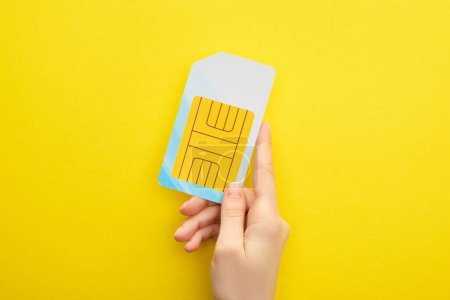 cropped view of woman holding sim card on yellow background