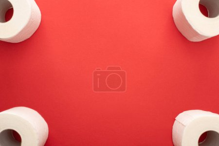 top view of white toilet paper rolls on red background with copy space